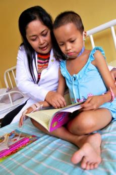 Infirmière philippine et petite fille hospitalisée lisant ensemble